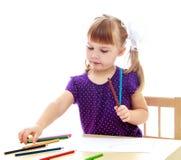 Nette Zeichnung des kleinen Mädchens mit Markierungen am Tisch Stockbilder