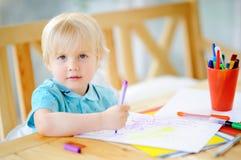 Nette Zeichnung und Malerei des kleinen Jungen mit bunten Markierungsstiften am Kindergarten lizenzfreie stockfotos