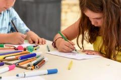 Nette Zeichnung und Malerei des kleinen Mädchens am Kindergarten Kreativer Tätigkeitskinderverein stockbilder