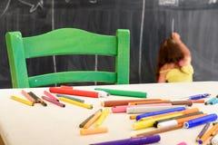 Nette Zeichnung und Malerei des kleinen Mädchens am Kindergarten Kreativer Tätigkeitskinderverein stockfotografie