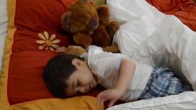 Nette zwei Jahre alte Junge, die Teddybären in Eltern einsetzen, gehen zu Bett, um zu schlafen stock video footage