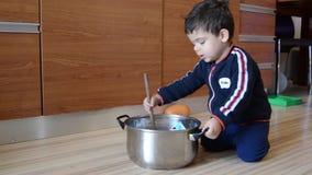 Nette zwei Jahre alte Junge, die vort?uschen, Suppe von der Babykleidung und -papier zu kochen stock video