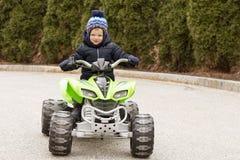 Nette zwei Jahre Kleinkind, die großes grünes Auto fahren stockbilder