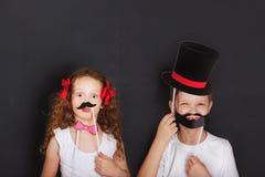 Nette Zwillingskinder halten Karnevalsschnurrbart und trotzen, Vatertagsbetrug Stockbilder