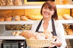 Netter älterer Bäcker verkauft gebackene Produkte Stockbild