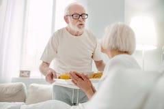 Netter älterer Mann, der für seine Frau sich interessiert stockbild