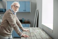 Netter älterer Mann, der in der Küche steht stockfotografie