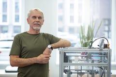 Netter älterer Mann, der nahe Drucker 3D aufwirft stockfotos