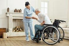Netter älterer Mann, der vom Rollstuhl hinausgeht stockfotografie