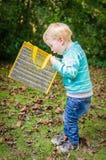Netter überraschter kleiner blonder Junge, der die innere Tasche im Freien schaut Lizenzfreie Stockbilder