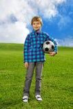 Netter überzeugter Junge mit Kugel Lizenzfreie Stockfotografie