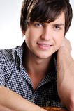 Netter überzeugter junger Kerl mit wenigem Lächeln Lizenzfreies Stockbild