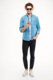 Netter überzeugter junger Mann im Hut und in der Sonnenbrille unter Verwendung des Smartphone Lizenzfreie Stockfotos