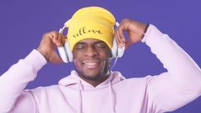 Netter afro-amerikanischer Mann in den Kopfh?rern gekleidet in der Stra?enartabnutzung, h?rend Musik stock footage