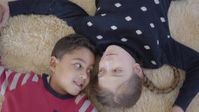 Netter Afroamerikanerjunge des Portr?ts und blondes kaukasisches M?dchen, die auf dem Boden auf dem beige flaumigen Teppich liegt stock footage