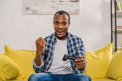 netter Afroamerikanermann, der an der Kamera beim Spielen mit Steuerknüppel lächelt lizenzfreie stockbilder