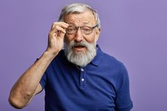 Netter alter Mann, der durch die Gläser der Kamera betrachtet lizenzfreies stockfoto
