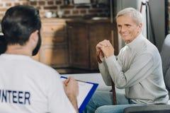 Netter alter Mann, der mit einem Freiwilligen spricht Stockfotos