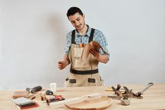 Netter angenehmer bärtiger Schreiner bei der Arbeit an seiner Werkstatt lizenzfreie stockfotos