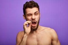 Netter angenehmer Mann, der Nasenhaar mit Pinzette entfernt lizenzfreie stockfotos
