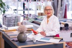 Netter anziehender Senior Manager, der an ihrem Schreibtisch sitzt stockfotografie