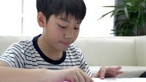 Netter asiatischer jugendlich Junge, der zu Hause Ihre Hausarbeit tut stock footage