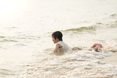 Netter asiatischer Junge, der auf dem Strand spielt Lizenzfreie Stockfotografie