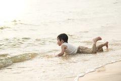 Netter asiatischer Junge, der auf dem Strand spielt Stockfotografie