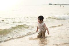 Netter asiatischer Junge, der auf dem Strand spielt Stockbild