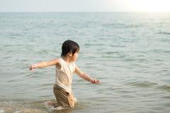 Netter asiatischer Junge, der auf dem Strand spielt Lizenzfreie Stockfotos