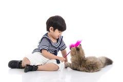 Netter asiatischer Junge, der mit Kätzchen der getigerten Katze spielt lizenzfreies stockfoto