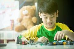 Netter asiatischer Junge, der mit Plastikblöcken spielt lizenzfreie stockbilder