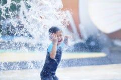 Netter asiatischer Junge, der am Wasserpark spielt Stockfotos