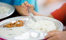 Netter asiatischer Kinderjunge, der Nahrungsmittel durch Selbst isst Kind, das einen Löffel hält stockfotos