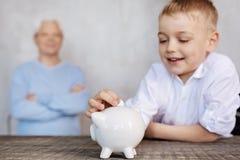 Netter aufgeregter Junge, der eine Münze in ein Sparschwein einsetzt Lizenzfreie Stockfotos