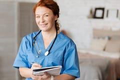 Netter ausgezeichneter Doktor, der zu Hause Beratung hält Lizenzfreie Stockfotografie