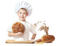 Netter Bäckerjunge mit einem Laib des Roggenbrotes Stockfotos