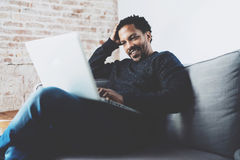 Netter bärtiger afrikanischer Mann, der an Laptop beim Sitzen des Sofas in seinem modernen Innenministerium arbeitet Konzept von  Stockbild