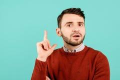 Netter bärtiger junger Mann in der zufälligen Ausstattung auf cyan-blauem Hintergrund stockfoto