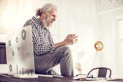 Netter bärtiger Mann, der Schirm seines Geräts betrachtet lizenzfreie stockfotos