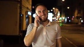 Netter bärtiger Mann haben einen Handyanruf Er beantwortet es und beginnt zum Plaudern mit jemand Aufenthalt auf Nachtstraße here stock video footage