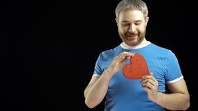 Netter bärtiger Mann im blauen T-Shirt hält eine rote Herzform stock footage