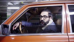 Netter bärtiger Mann mit dem langen dunklen Haar öffnet rotes Autofenster und fängt an zu sprechen stock footage