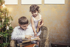 Netter Babyjunge und -mädchen in einem Stuhl ein Buch in einem Innenraum lesend Stockbilder