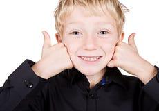 Netter blonder behaarter Junge, der mit den Daumen oben lächelt Lizenzfreie Stockfotografie