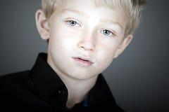 Netter blonder behaarter Junge, der nachdenklich schaut Lizenzfreie Stockbilder