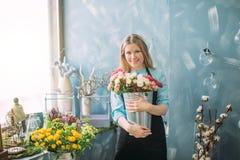 Netter blonder Florist, der nahe dem Fenster mit Blumen steht Stockfotografie