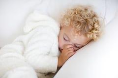 Netter blonder gelockter kleiner Junge, der auf weißer Couch schläft Stockbilder