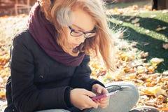 Netter blonder Jugendliche usin Smartphone Stockfotos