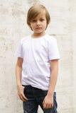 Netter blonder Junge in den Jeans und in einem weißen Hemd Stockbilder